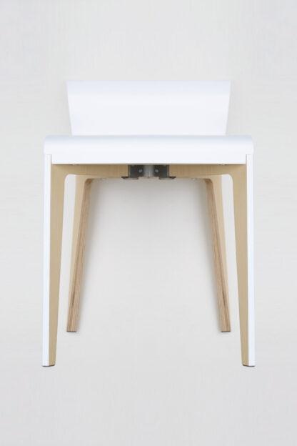 Chaise en bois clair de bouleau recouverte en surface d'une laque blanche.