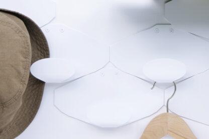 Porte manteau mural en métal blanc avec cintre en bois et chapeau accrochés.