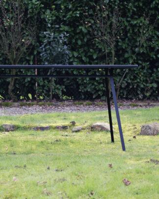 Table en métal noir dans une finition mat avec plateau amovible pour 4 à 6 personnes.
