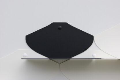 Une petite étagère murale noire en métal parmi des blanches, dans un fini texturé mat.