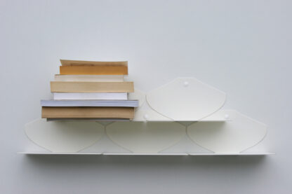 Petites étagères en métal blanc mat disposées en damier avec livres de poches empilés.