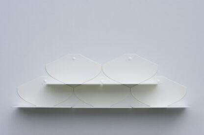Étagères murales en métal blanc au design en forme d'écaille, groupées.