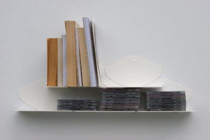 Tablettes murales blanches en métal plié sur lesquelles sont posés livres et cd.