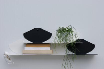 Étagères murales noires et blanches avec livres de poches et une petite plante verte.