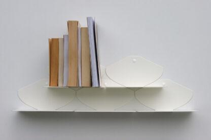Étagères murales blanches fines, en métal, mates, avec livres de poche rangés.