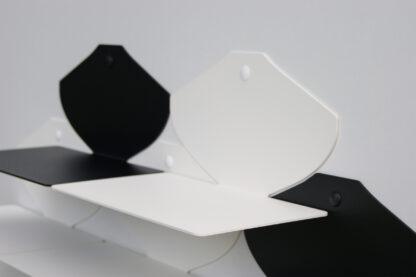 Cinq petites tablettes murales en métal noires et blanches disposées en damier.